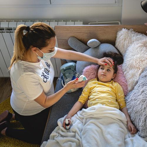 Caregiver taking temperature covid-square